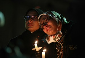 Two women watch speakers during a vigil following the deaths of students Deah Shaddy Barakat, Yusor Mohammad, Razan Mohammad Abu-Salha at the University of North Carolina at Chapel Hill.